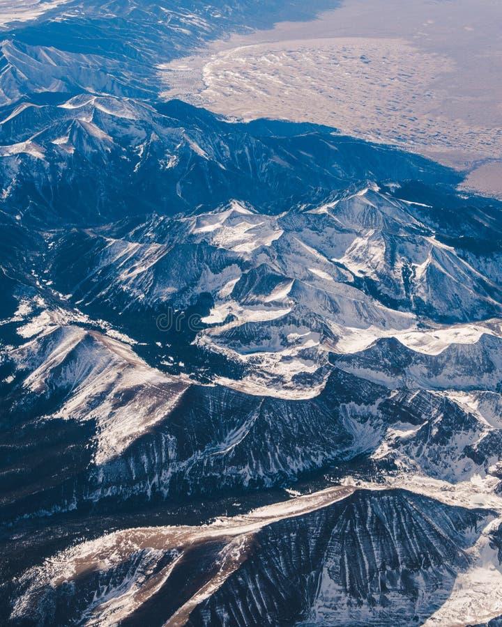 Χιονώδης σειρά βουνών από το αεροπλάνο στοκ εικόνα