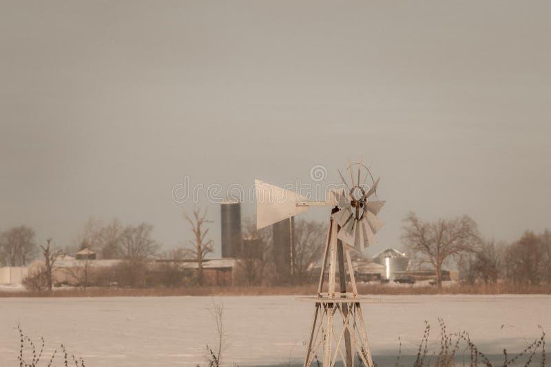 Χιονώδης σκηνή χειμερινών γαλακτοκομικών αγροκτημάτων απόχρωσης σεπιών με τον ανεμόμυλο, κομητεία δεσμών, Ιλλινόις στοκ εικόνες