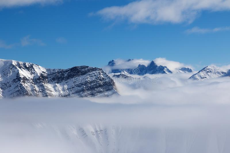Χιονώδη βουνά φωτός του ήλιου στην ελαφριά ομίχλη και το μπλε ουρανό στη συμπαθητική ημέρα ήλιων στοκ φωτογραφία