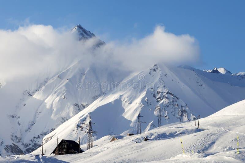 Χιονώδη κλίση και ξενοδοχείο σκι στα υψηλά βουνά στο χειμερινό βράδυ στοκ φωτογραφία