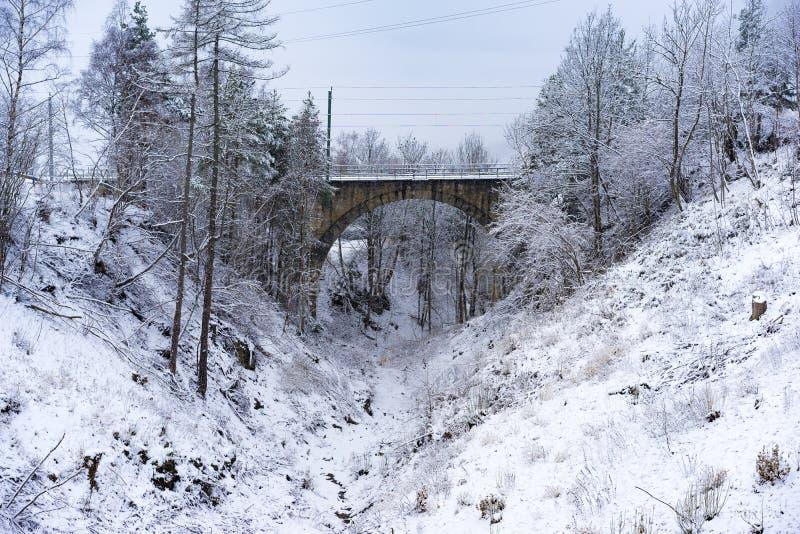 Χιονώδης κοιλάδα με μια σχηματισμένη αψίδα γέφυρα στοκ εικόνες με δικαίωμα ελεύθερης χρήσης