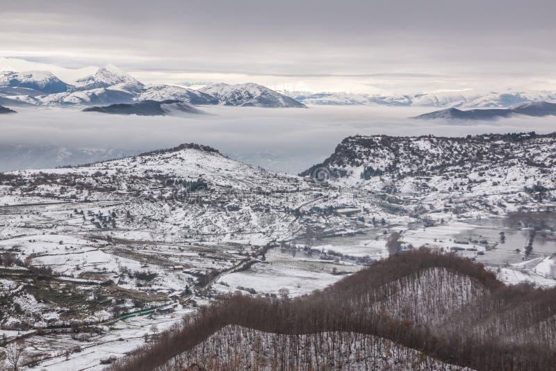 Χιονώδη βουνά με την ομίχλη στοκ εικόνα