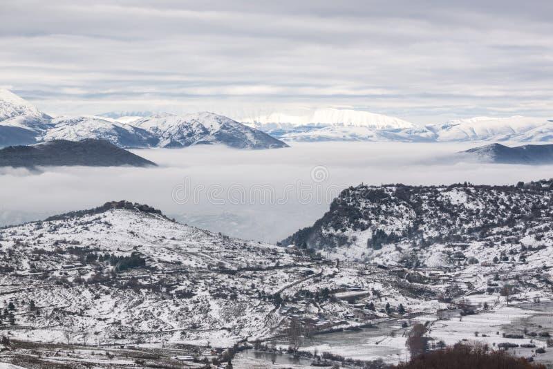 Χιονώδη βουνά με την ομίχλη στοκ φωτογραφία