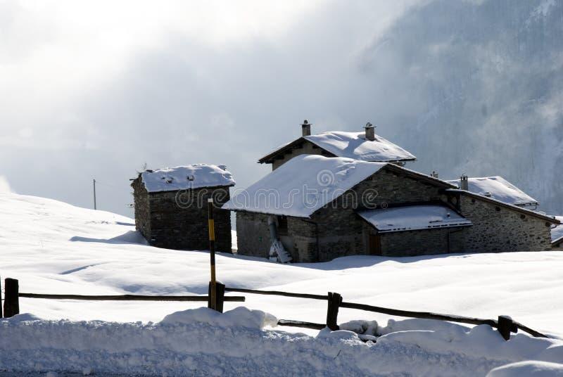 χιόνι βουνών καλυβών κάτω στοκ φωτογραφία