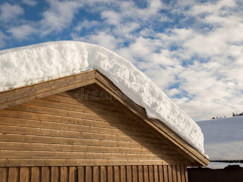 Χιόνι σε μια στέγη ενός καφετιού κτηρίου, άσπρα σύννεφα στο μπλε ουρανό στοκ φωτογραφία