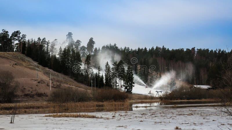 Χιόνι ψεκασμού πυροβόλων χιονιού στο λόφο slalom χωρίς χιόνι στοκ εικόνες