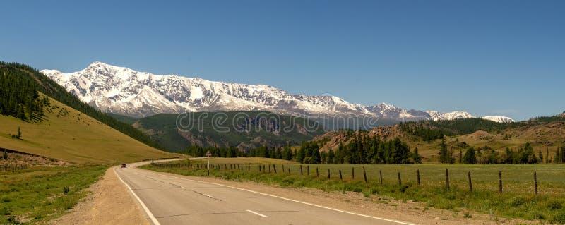 Χιόνι Altai κορυφογραμμών Chuya πανοράματος βουνών και ο δρόμος, Ρωσία, Ιούνιος στοκ φωτογραφία
