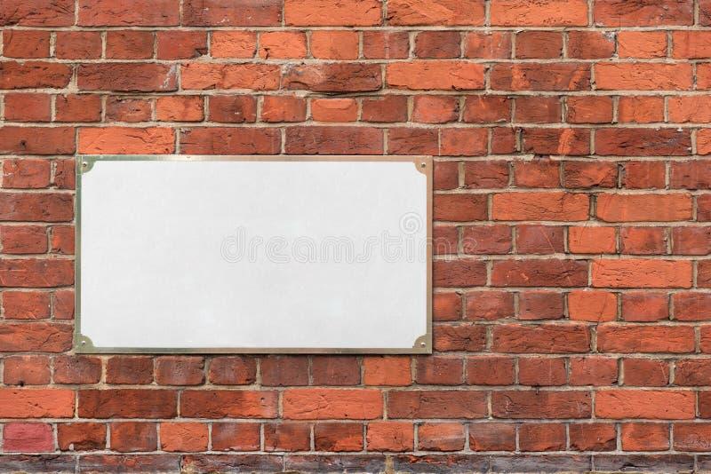 Χλεύη επάνω με το κενό κενό άσπρο σημάδι διευθύνσεων στο τουβλότοιχο στοκ φωτογραφία