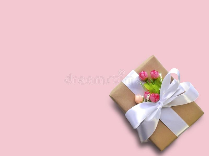 Χλεύη επάνω στην εικόνα του κιβωτίου δώρων με τα λουλούδια στο ρόδινο υπόβαθρο στοκ φωτογραφία