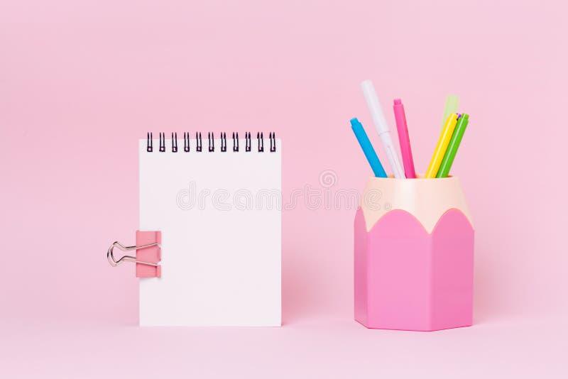 Χλεύη επάνω στην εικόνα των κενών προμηθειών σημειωματάριων και γραφείων, κάτοχος μολυβιών στο ρόδινο υπόβαθρο στοκ φωτογραφία με δικαίωμα ελεύθερης χρήσης