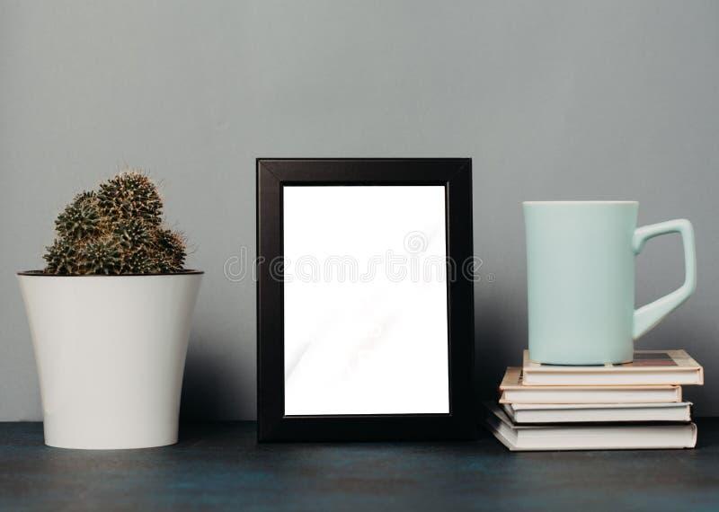 Χλεύη επάνω στη φωτογραφία με το πλαίσιο και το φλυτζάνι του τσαγιού ή του καφέ και των βιβλίων και του κάκτου κλείστε επάνω στοκ φωτογραφία με δικαίωμα ελεύθερης χρήσης