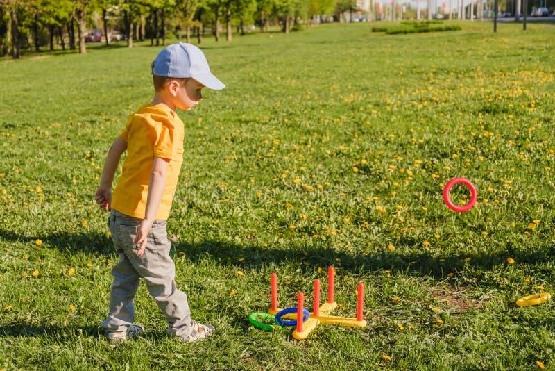 Χλόη διασκέδασης αγοριών παιδιών παιχνιδιού οικογενειακή εκτίναξη στοκ εικόνες