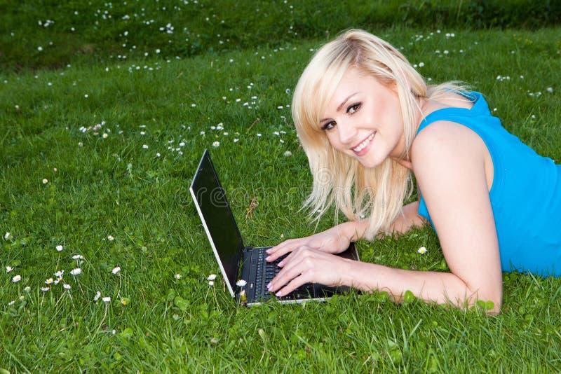 χλόη το lap-top της που χαμογελά χρησιμοποιώντας τη γυναίκα στοκ φωτογραφίες με δικαίωμα ελεύθερης χρήσης
