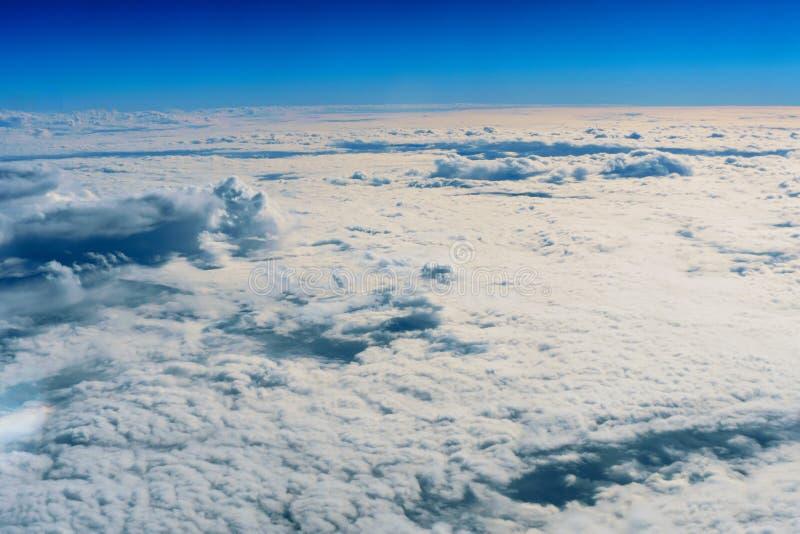 Χνουδωτοί άσπροι σύννεφα και μπλε ουρανός από το αεροπλάνο στοκ εικόνες με δικαίωμα ελεύθερης χρήσης