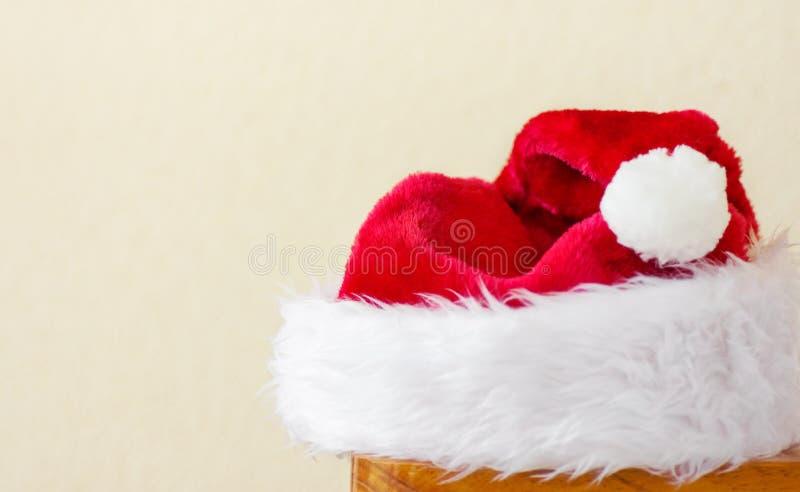 Χνουδωτό καπέλο Άγιου Βασίλη που βρίσκεται στο ξύλινο υπόβαθρο τοίχων σκαμνιών άσπρο Νέο έμβλημα αφισών ετών Χριστουγέννων με το  στοκ εικόνα με δικαίωμα ελεύθερης χρήσης