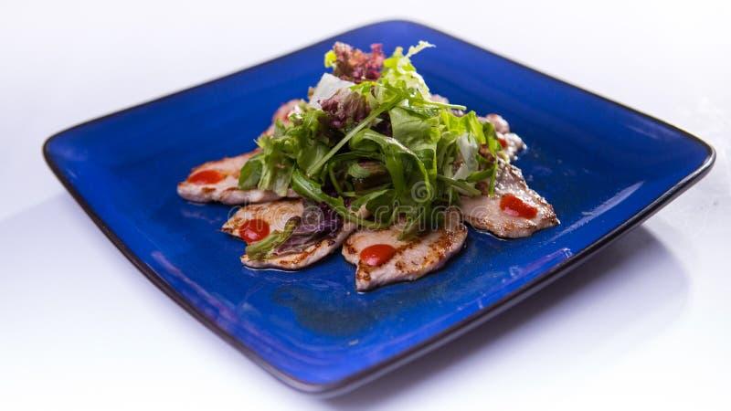 Χοιρινό κρέας με τη σαλάτα πιπεροριζών και μιγμάτων στο μπλε κινεζικό πιάτο στο άσπρο β στοκ φωτογραφία