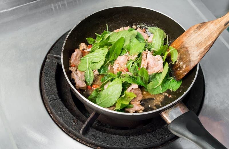 Χοιρινό κρέας τηγανητών με το βασιλικό στο τηγάνισμα του τηγανιού στοκ εικόνες