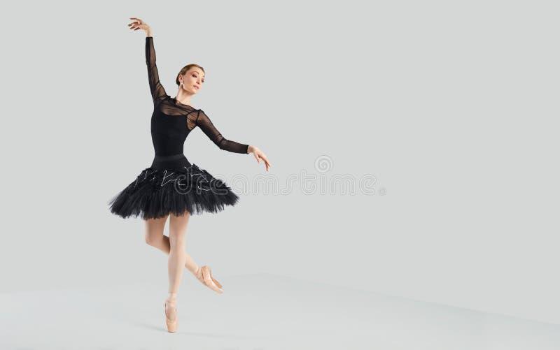 Χορευτής μπαλέτου γυναικών πέρα από το γκρίζο υπόβαθρο στοκ εικόνα με δικαίωμα ελεύθερης χρήσης