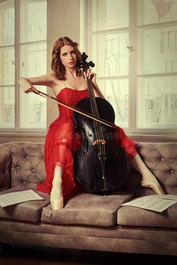 Χορευτής μπαλέτου στο κόκκινο φόρεμα και pointe παιχνίδι στο παλαιό μαύρο βιολοντσέλο στοκ φωτογραφία