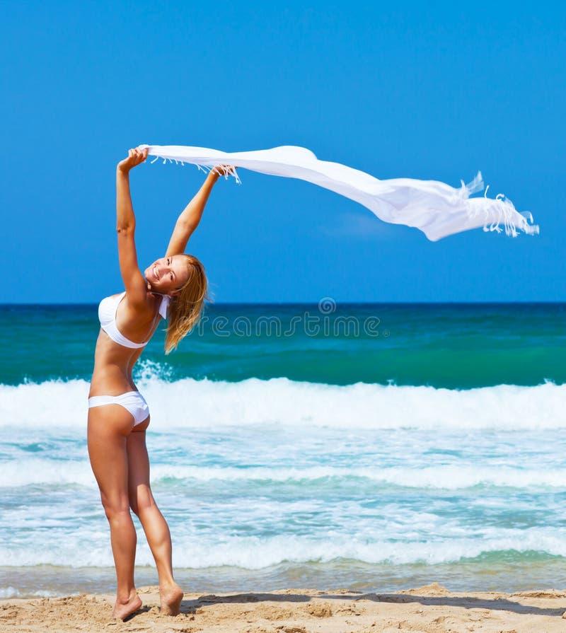Χορεύοντας ευτυχές κορίτσι στην παραλία στοκ φωτογραφία
