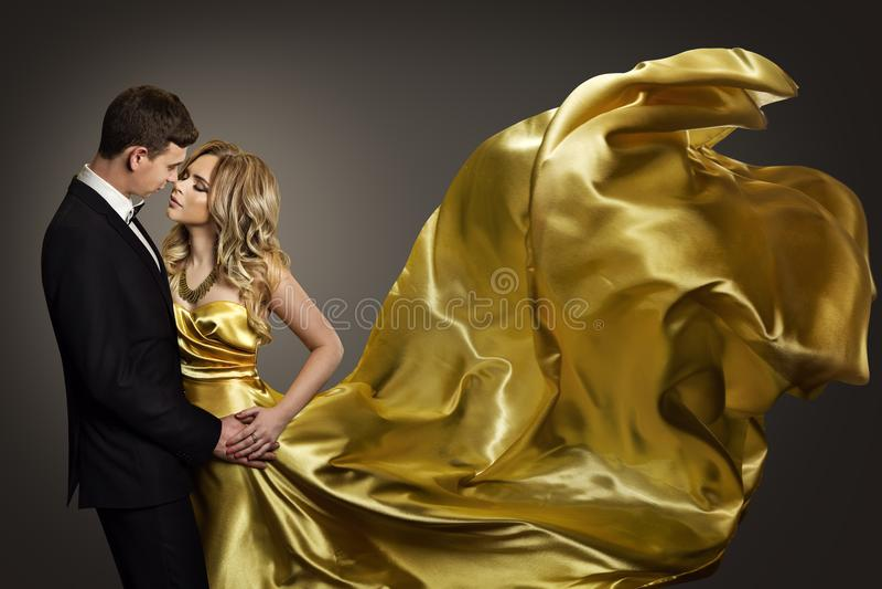 Χορεύοντας, κομψοί άνδρας ζεύγους και γυναίκα, πρότυπο χρυσό φόρεμα μόδας στοκ εικόνα