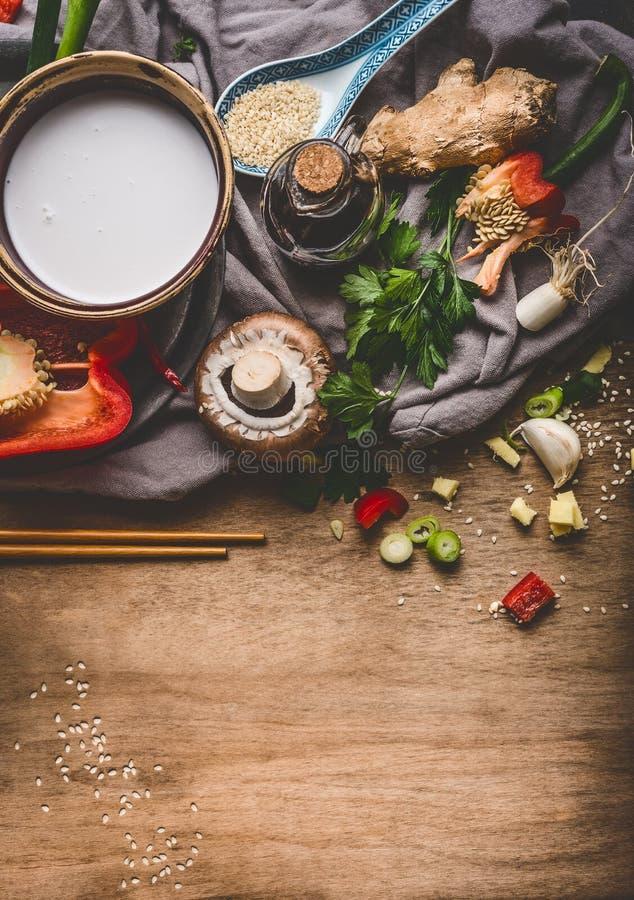 Χορτοφάγα ασιατικά συστατικά κουζίνας με τα τεμαχισμένα λαχανικά, το γάλα καρύδων, τους σπόρους, τα καρυκεύματα και chopsticks στ στοκ φωτογραφία