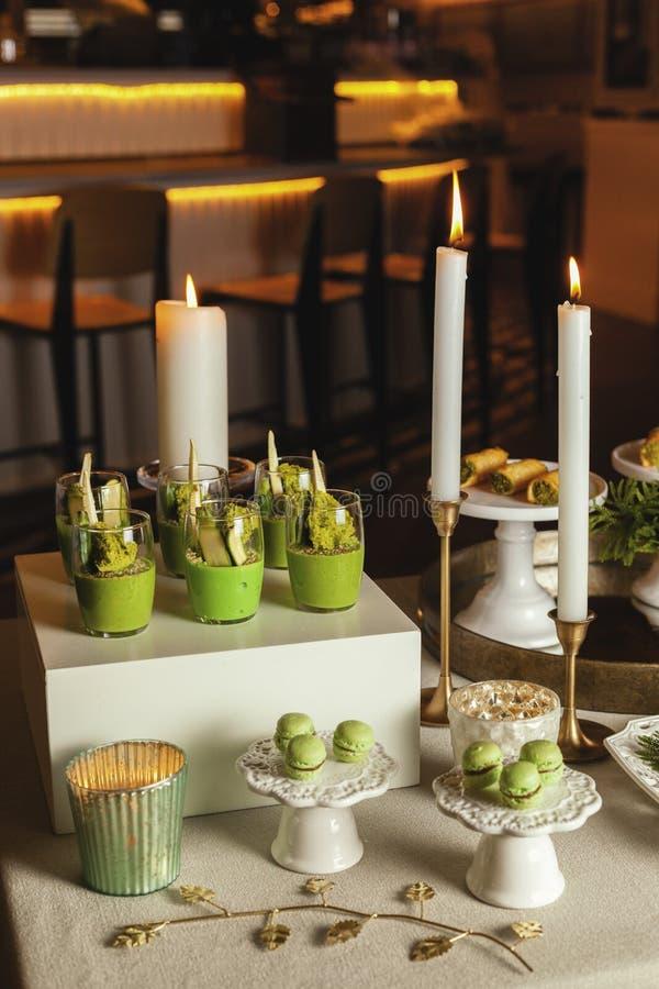 Χορτοφάγα τρόφιμα Φλυτζάνια με Hummus που διακοσμούνται με τα λουλούδια, muffins στον πίνακα καθορισμένο ύδωρ επιτραπέζιων ταινιώ στοκ εικόνες