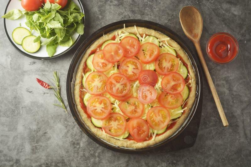 Χορτοφάγος πίτσα Διαδικασία μαγειρέματος της φυτικής σπιτικής πίτσας με τα φρέσκα συστατικά που απομονώνεται στο σκοτεινό υπόβαθρ στοκ εικόνες