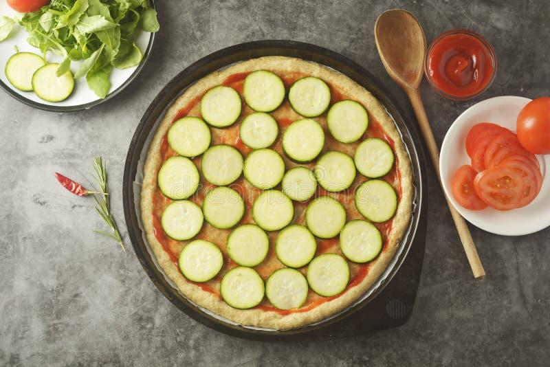 Χορτοφάγος πίτσα Διαδικασία μαγειρέματος της φυτικής σπιτικής πίτσας με τα φρέσκα συστατικά που απομονώνεται στο σκοτεινό υπόβαθρ στοκ εικόνα με δικαίωμα ελεύθερης χρήσης