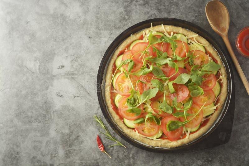 Χορτοφάγος πίτσα Διαδικασία μαγειρέματος της φυτικής σπιτικής πίτσας με τα φρέσκα συστατικά που απομονώνεται στο σκοτεινό υπόβαθρ στοκ φωτογραφία