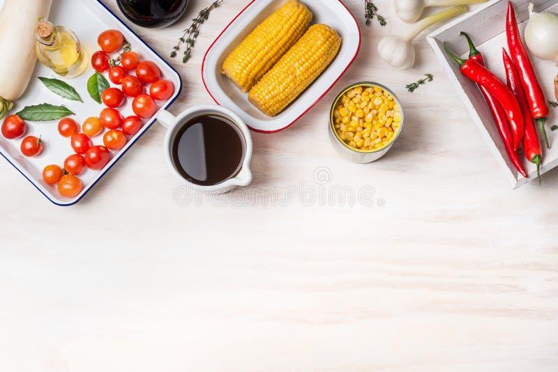 Χορτοφάγος προετοιμασία σούπας καλαμποκιού με το διάφορο καλαμπόκι, το ζωμό και τα μαγειρεύοντας συστατικά στο άσπρο ξύλινο υπόβα στοκ εικόνες