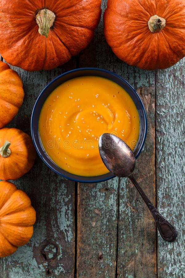 Χορτοφάγος σπιτική σούπα κολοκύθας που διακοσμείται με το φωτεινό πορτοκαλί PU στοκ φωτογραφία