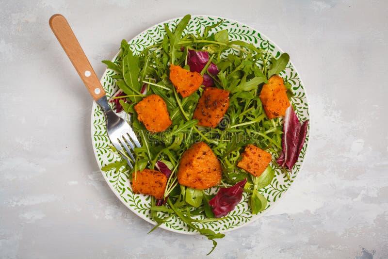 Χορτοφάγος φωτεινή σαλάτα της ψημένης γλυκιάς πατάτας με το arugula μόριο στοκ εικόνες