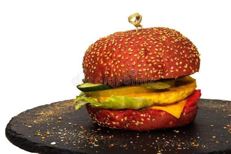 Χορτοφάγο burger με το τυρί, αγγούρια, γλυκά πιπέρια σε ένα μαύρο επίπεδο πιάτο πετρών στοκ εικόνα με δικαίωμα ελεύθερης χρήσης