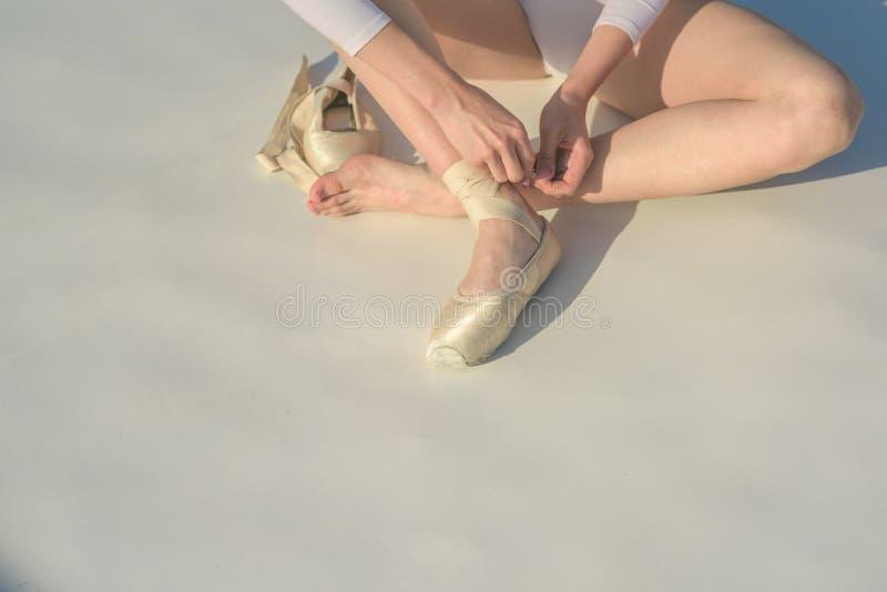 Χορός στο pointe Παπούτσια Ballerina Πόδια Ballerina στα άσπρα παπούτσια μπαλέτου Δέσιμο των παντοφλών μπαλέτου Θηλυκά πόδια στο  στοκ φωτογραφίες