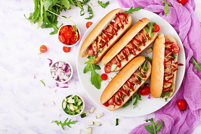 Χοτ-ντογκ με το λουκάνικο μπέϊκον, αγγούρι, ντομάτα και κόκκινο κρεμμύδι στο άσπρο πιάτο στοκ φωτογραφίες με δικαίωμα ελεύθερης χρήσης