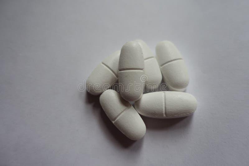 Χούφτα των άσπρων caplets του κιτρικού άλατος ασβεστίου στοκ εικόνα
