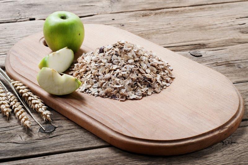Download Χούφτα Oatmeal σε έναν ξύλινο τέμνοντα πίνακα με τα μήλα Στοκ Εικόνες - εικόνα από ελεύθερος, υγιής: 62714292
