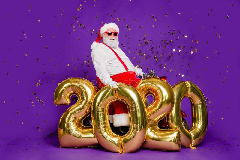 Χο-χο-χο Πλήρης φωτογραφία σώματος του παχιού άγιου βασίλη που κάθεται σε μοτοσικλέτα κρατώντας μεγάλα αερόστατα το νέο έτος 2020 στοκ φωτογραφία με δικαίωμα ελεύθερης χρήσης