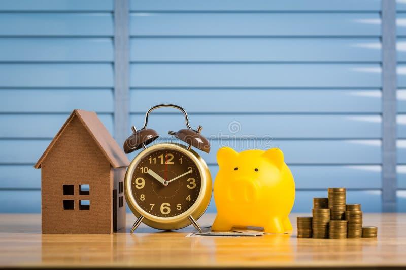Χρήματα αποταμίευσης για να αγοράσει ένα νέο σπίτι των χρημάτων του στη piggy τράπεζα Χαμηλότερο κόστος και φόρος στοκ φωτογραφία με δικαίωμα ελεύθερης χρήσης