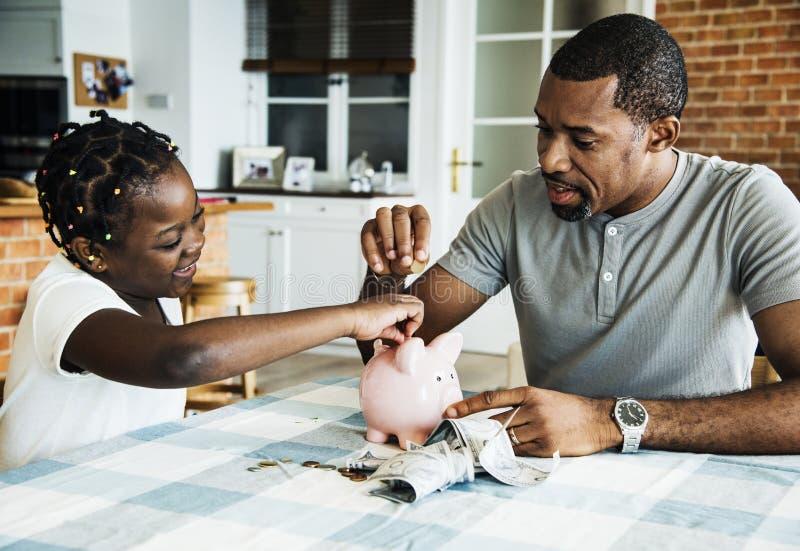 Χρήματα αποταμίευσης μπαμπάδων και κορών στη piggy τράπεζα στοκ εικόνες