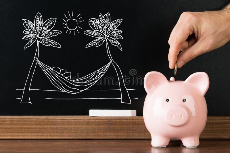 Χρήματα αποταμίευσης προσώπων σε Piggybank για τις διακοπές στοκ εικόνες