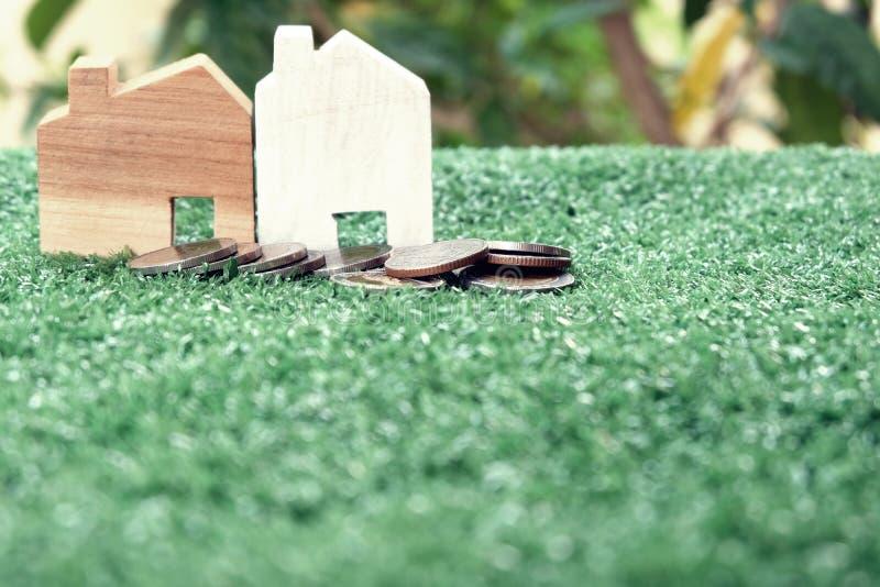 Χρήματα για την κατοικία Σωροί των νομισμάτων και του ξύλινου προτύπου σπιτιών στην πράσινη χλόη Εκλεκτική εστίαση στοκ φωτογραφίες με δικαίωμα ελεύθερης χρήσης