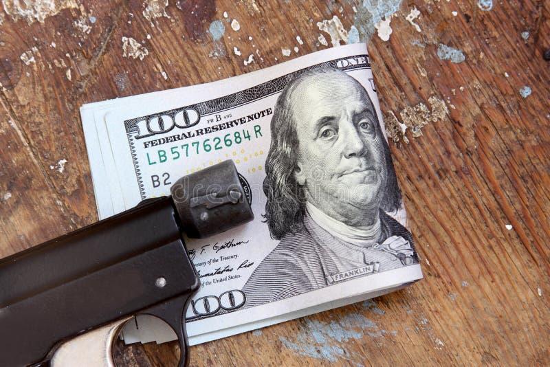 Χρήματα λογαριασμών δολαρίων με το πιστόλι στοκ φωτογραφίες