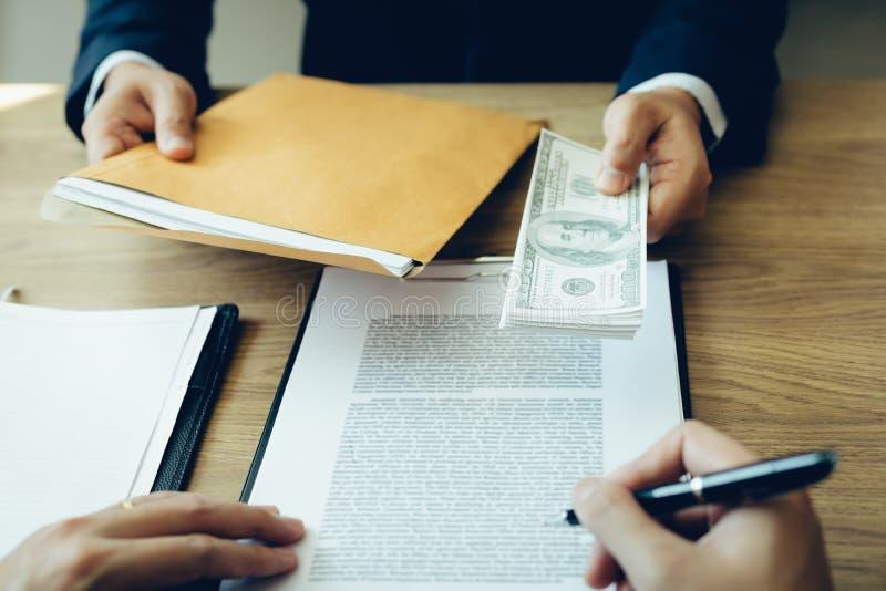 Χρήματα στα χέρια των επιχειρηματιών που υποβάλλουν στους επιχειρηματίες για να αναγκάσουν την υπογραφή των εγγράφων συμβάσεων γι στοκ φωτογραφία με δικαίωμα ελεύθερης χρήσης