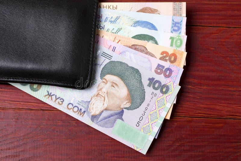 Χρήματα του Κιργισίου στο μαύρο πορτοφόλι στοκ φωτογραφία