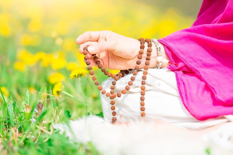 Χρήση Mala με τα mantras κατά τη διάρκεια μιας πρακτικής γιόγκας στοκ εικόνα με δικαίωμα ελεύθερης χρήσης