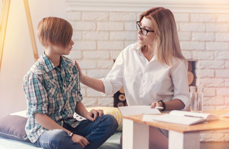 Χρήσιμος ψυχολόγος που μιλά με ένα σχολικό αγόρι στοκ εικόνα