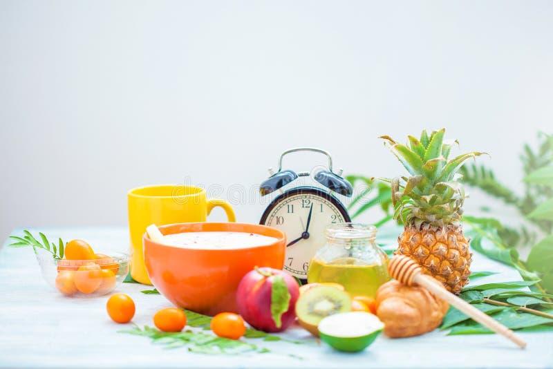 Χρήσιμο πρόγευμα πρωινού, muesli, φλιτζάνι του καφέ μελιού ανανά ασβέστη ροδάκινων φρούτων και ένα ξυπνητήρι σε ένα μπλε αντίγραφ στοκ φωτογραφίες
