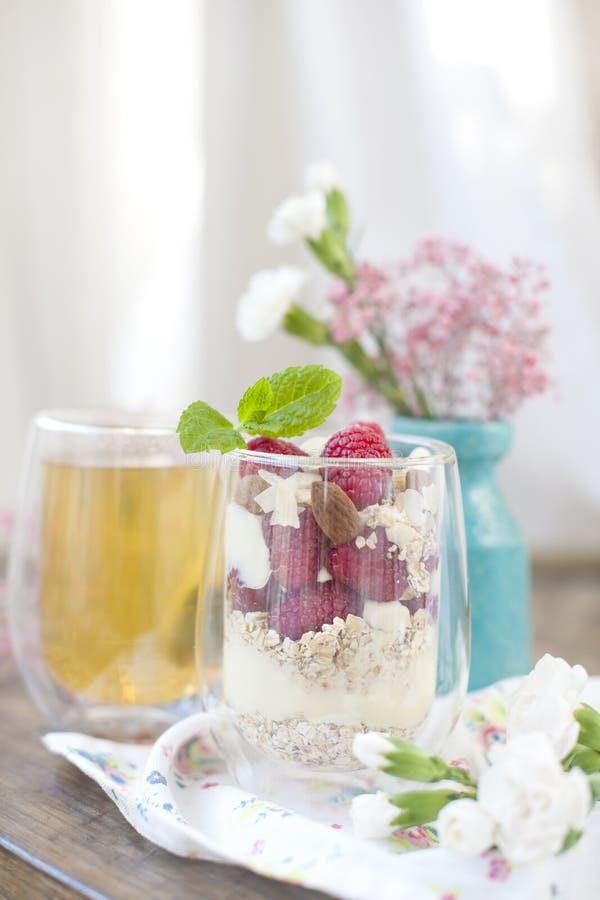 Χρήσιμο πρόγευμα του muesli και του γιαουρτιού με τα μούρα σε ένα γυαλί τσάι γυαλιού Μια ανθοδέσμη των λουλουδιών σε ένα μπλε βάζ στοκ φωτογραφία